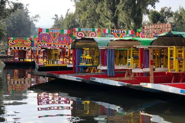 a small boat in a body of water with Xochimilco in the background