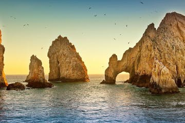 a large body of water with Arch of Cabo San Lucas in the background