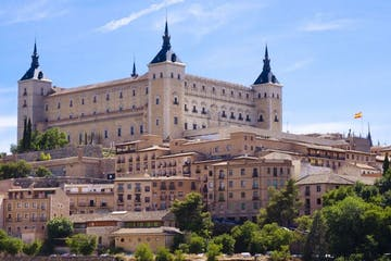 a castle with a clock at the top of Alcázar of Toledo