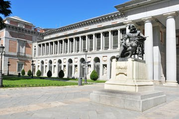a large stone statue in front of Museo del Prado