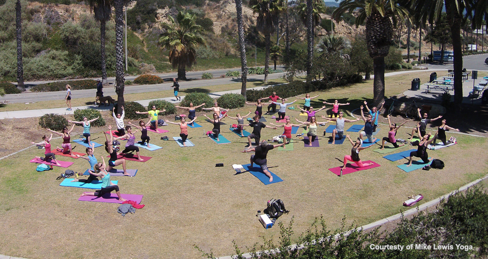 Group of people performing yoga at Leadbetter Beach in Santa Barbara with Yoga Mike