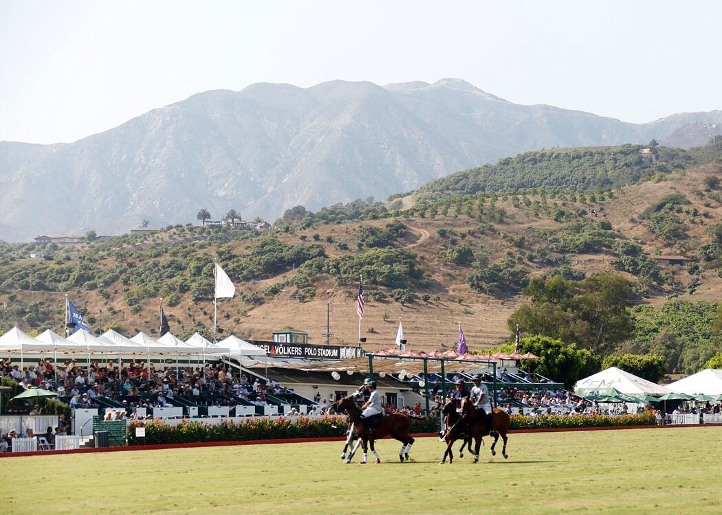 The Santa Barbara Polo grandstands with riders riding on the polo field in Summerland
