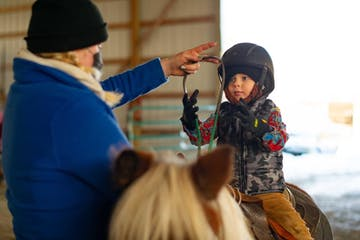 a child in a riding lesson
