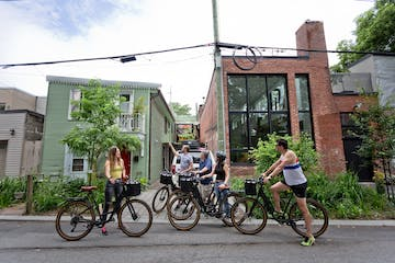 group of people on bikes with houses in background