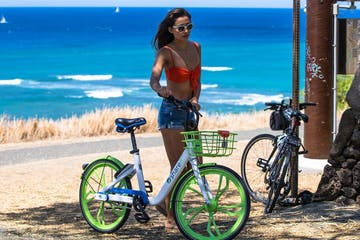 a person with a bicycle in front of a beach