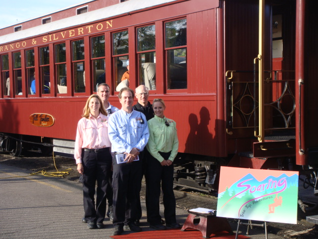 A group of Soaring Tree Top Adventures staff members wait next to the Durango Silverton Narrow Gauge Railroad.
