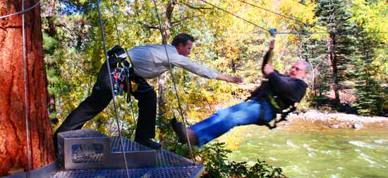 A Sky Ranger helps a zipliner reach a tree platform at Soaring Tree Top Adventures.