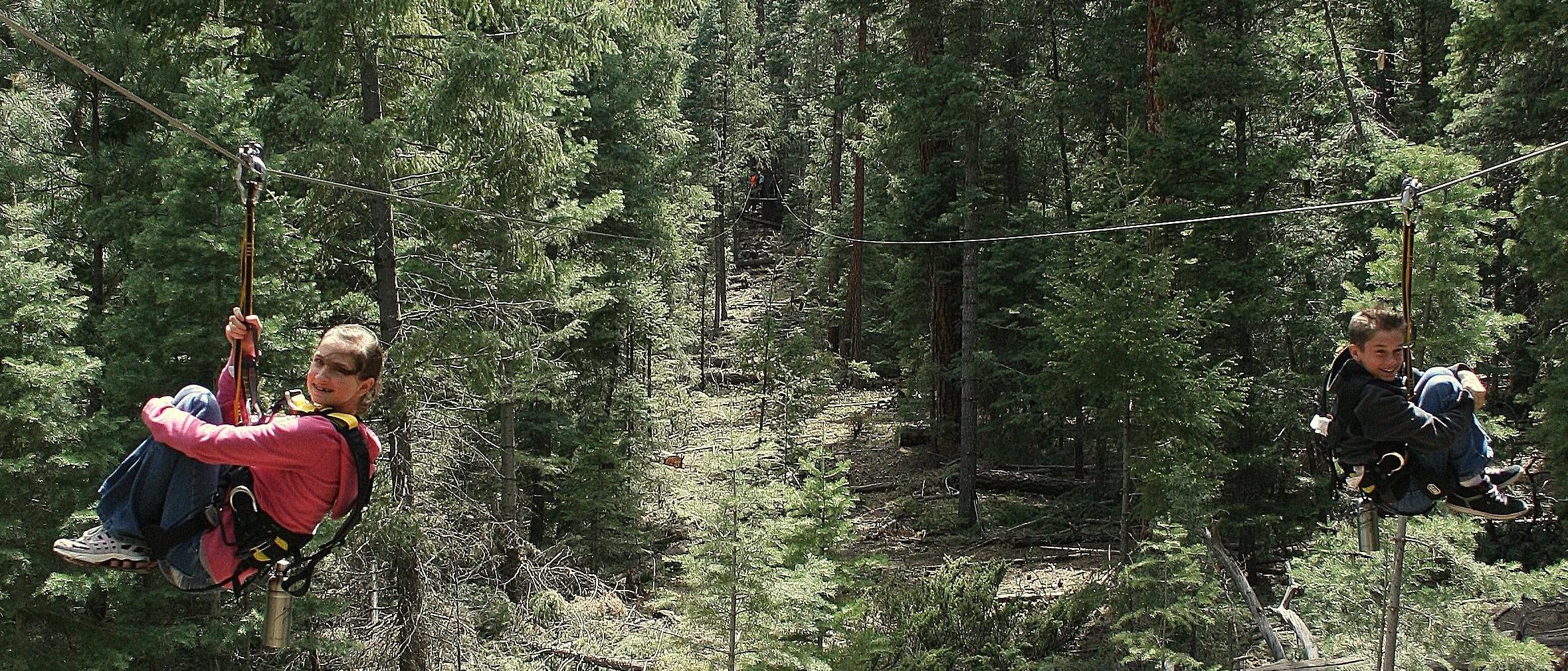 A boy and girl race down zipline spans.