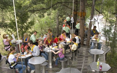 A group of Soaring Tree Top Adventures visitors eat lunch in the trees.