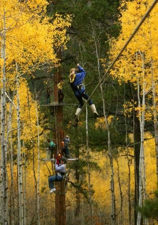 Several visitors zipline through the fall trees.
