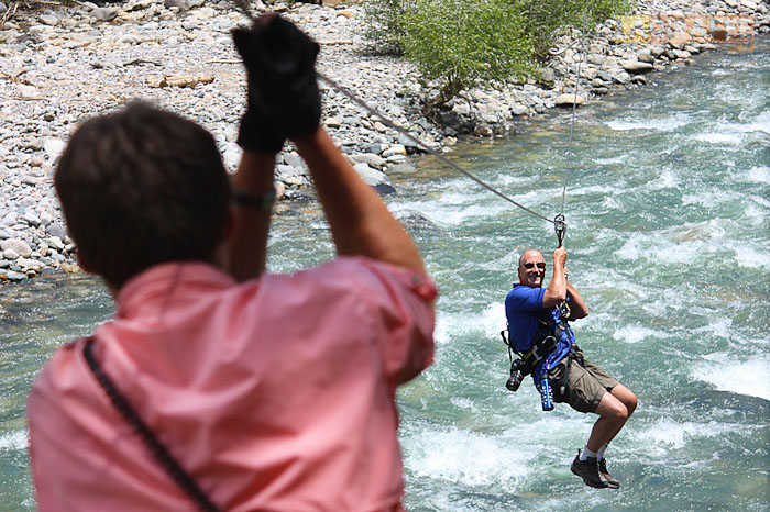 A zipliner crosses a span over the Animas River.