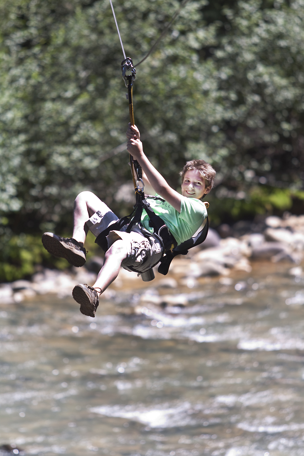 A boy ziplines over the Animas River at Soaring Tree Top Adventures.