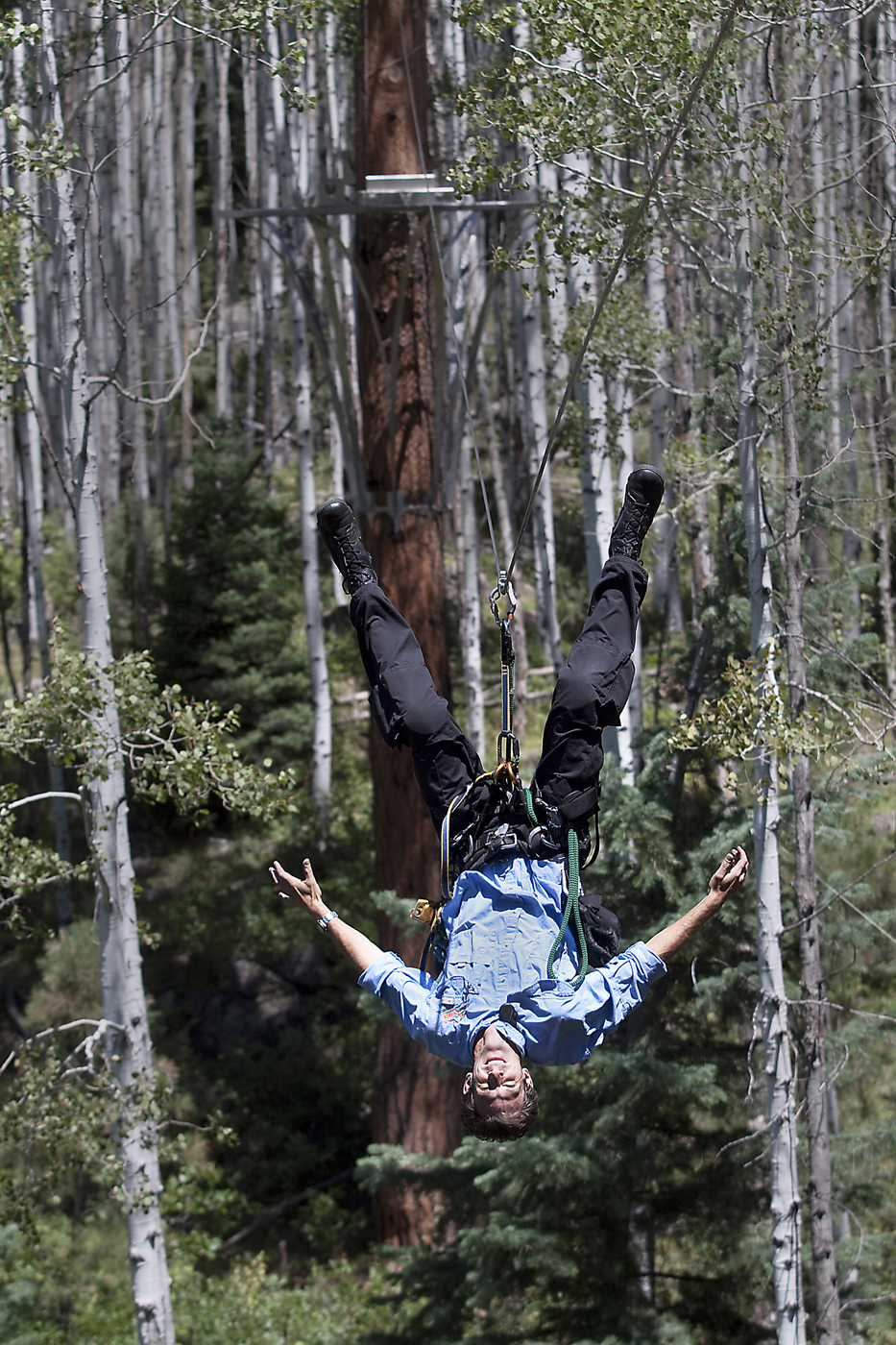 A zipline visitor ziplines upside down and hands-free at Soaring Tree Top Adventures.