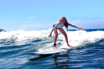 a young girl riding a wave on a surfboard in the water