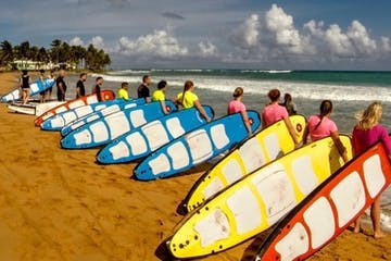 a group of people carrying surfboards on top of a sandy beach