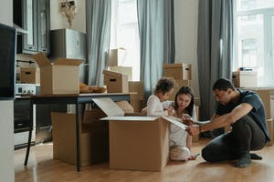 A family sitting next to moving boxes