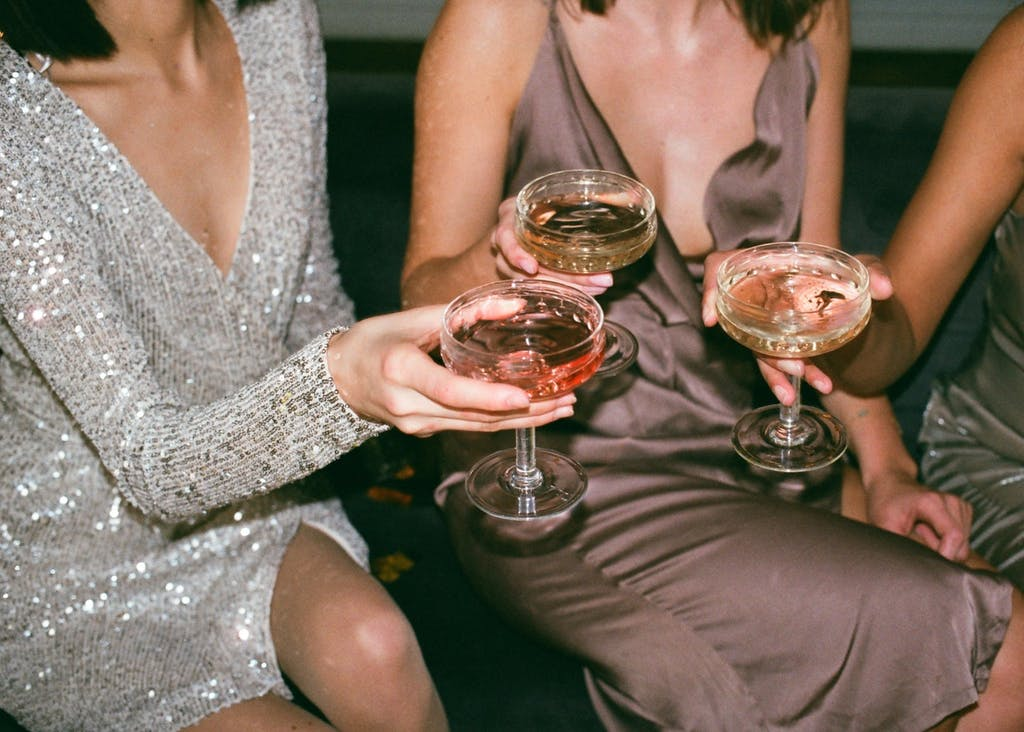 Three women in party dresses drink champagne.