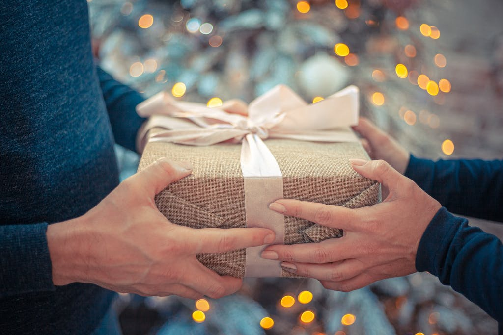 Two sets of hands holding a wrapped gift
