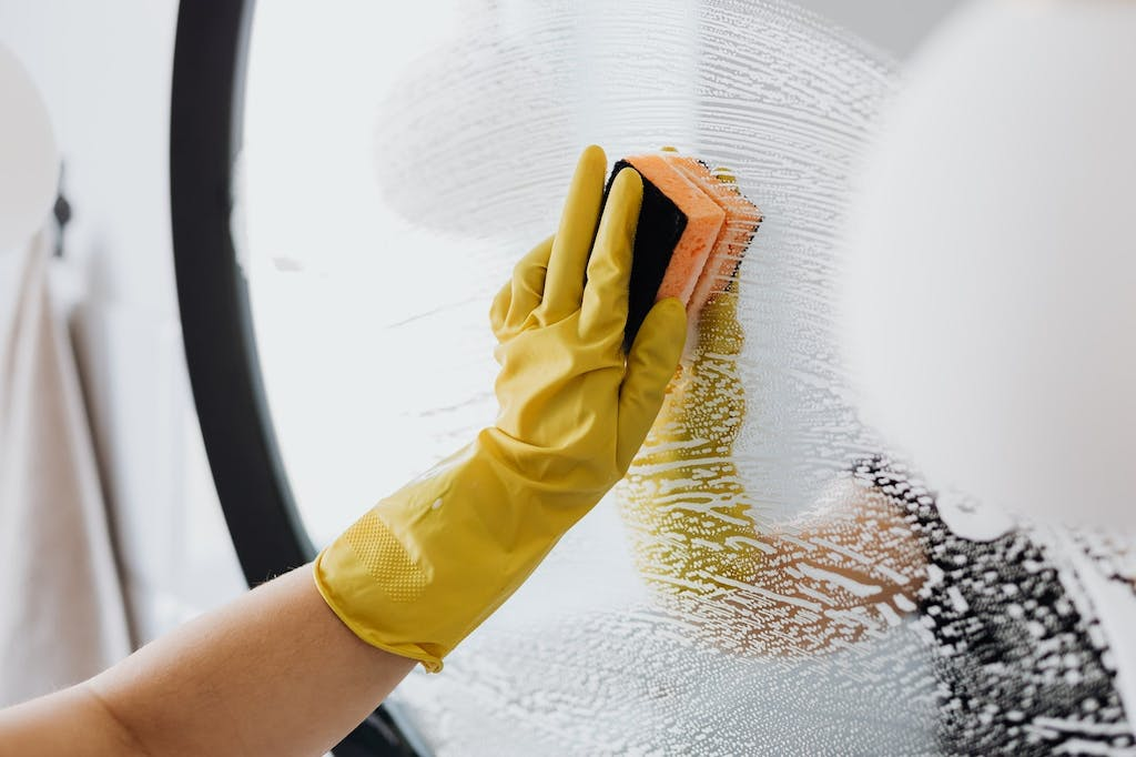 A person cleaning a mirror with a sponge before throwing a last-minute housewarming party.