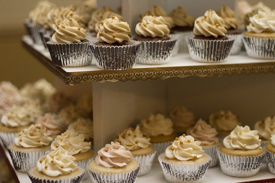 many cupcakes lined up on two sheets.