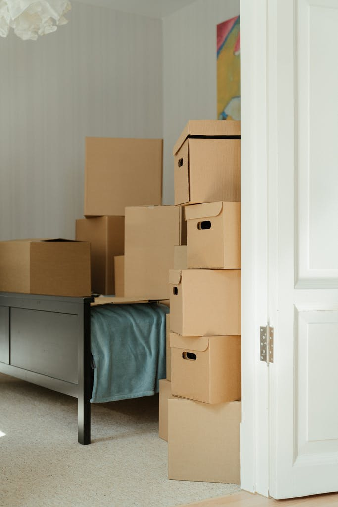 a door, a bed, and a stack of boxes