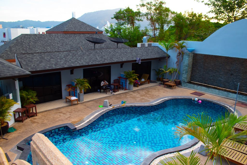 a house with a pool and palm trees