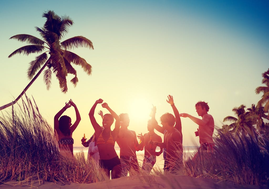 A group of people dancing at the beach.