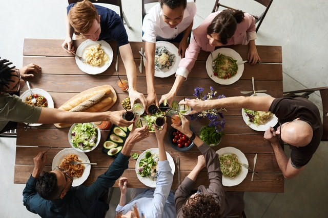 a group of people sitting at a table with food