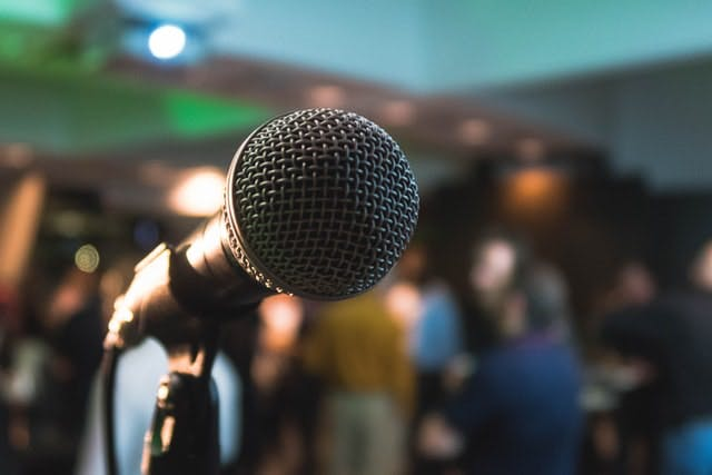 a man holding a microphone in front of a crowd
