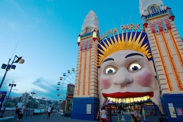 a close up of a person with Luna Park Sydney in the background
