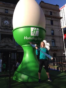 a woman standing in front of a green building