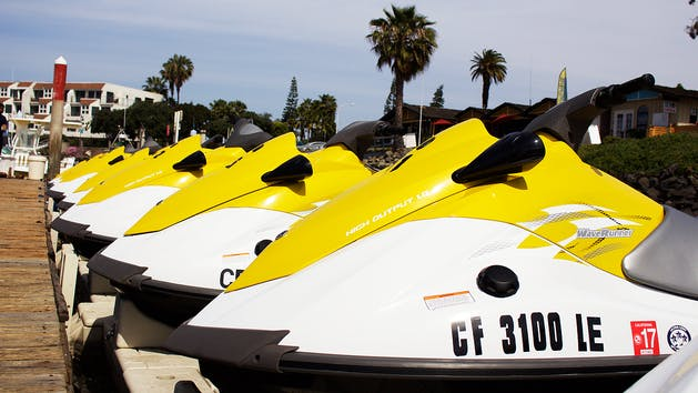 Yellow WaveRunners lined up in a marina