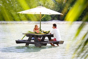 A couple having water lunch on a private island in Bora Bora