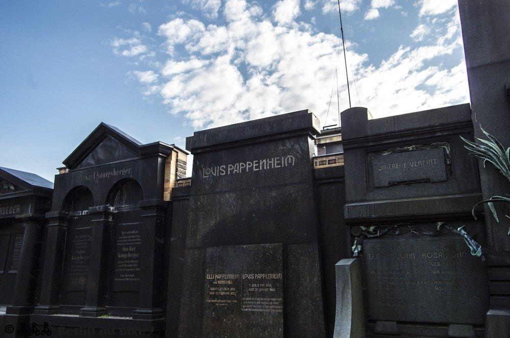 Schwarze Grabsteine vor dramatischem Himmel auf dem jüdischen Friedhof Weissensee.