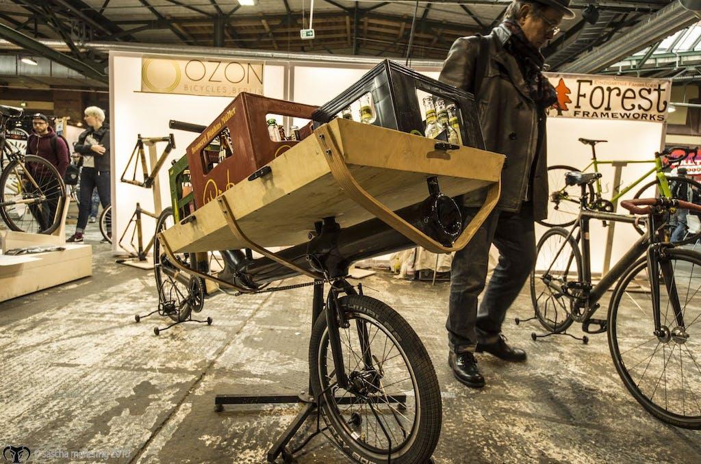 a bicycle parked Ozone-Cyclery bei denen Ihr in mehrtägigen Workshops Euer eigenes individuelles Bambusrad bauen könnt, zeigen ein ziemlich außergewöhnliches Cargobike. Sieht ein bißchen aus wie ein Kanonenrohr, findet Ihr nicht?on the side of a building