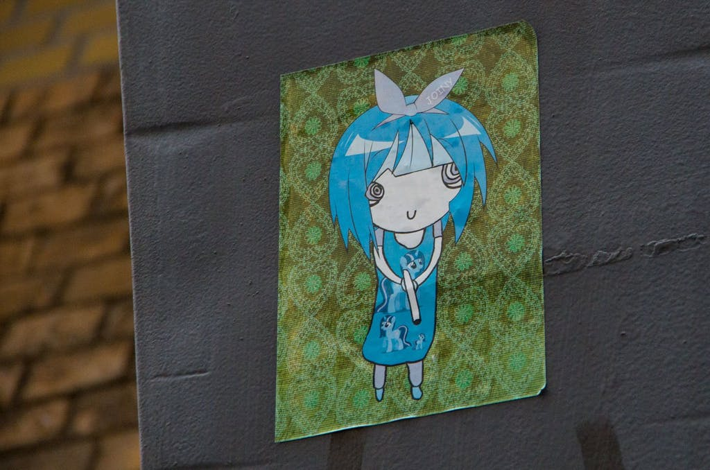 Street Art in Berlin Mitte: Noch ein süßes Killer-Manga-Mädchen mit Drogen im Kopf und einer Waffe in der Hand.