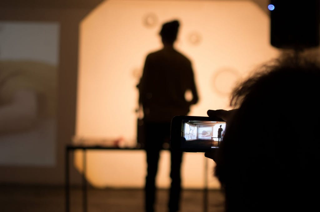 Eine Besucherin filmt eine Performance mit Ihrem Smartphone.
