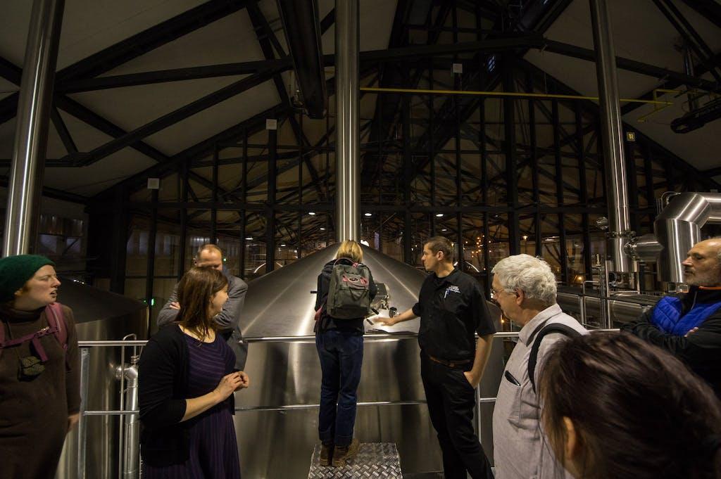 Besucher blicken in den Braukessel bei Stone Brewing Berlin