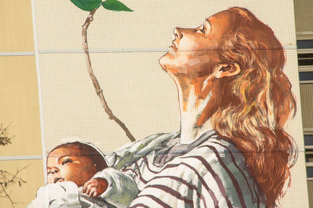 Wandgemälde in Berlin Tegel, Detail aus The Circle of Life von Fintan Magee: Frau mit Säugling