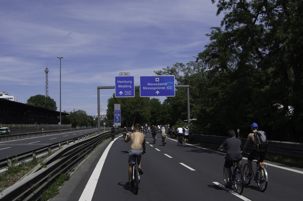 a group of people riding bikes down a highway