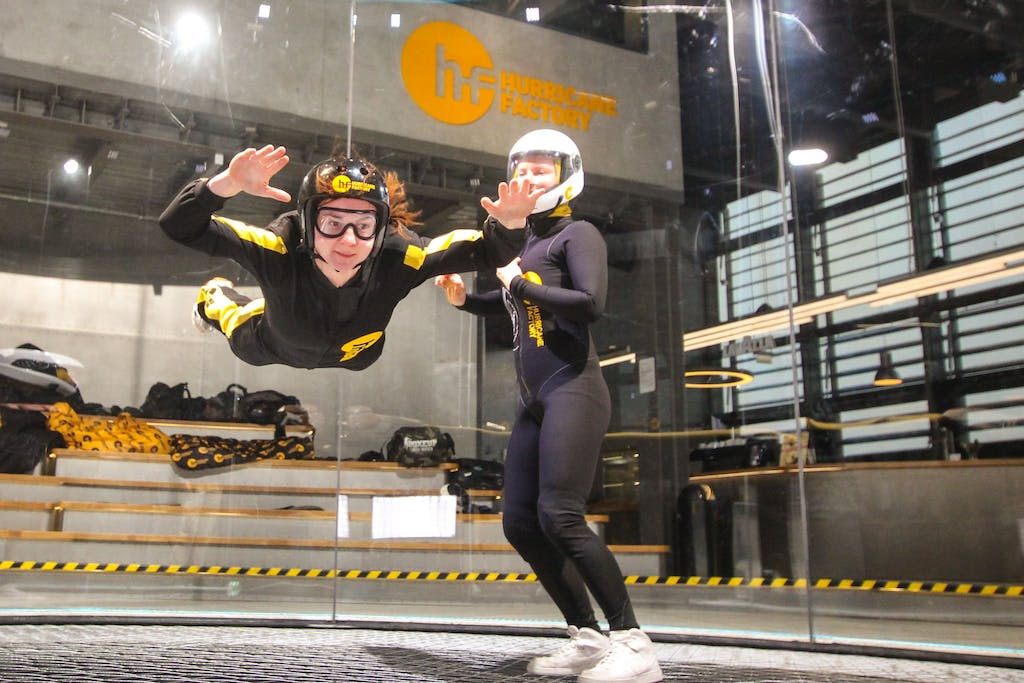 Two women in a wind tunnel in Berlin, one holding the other