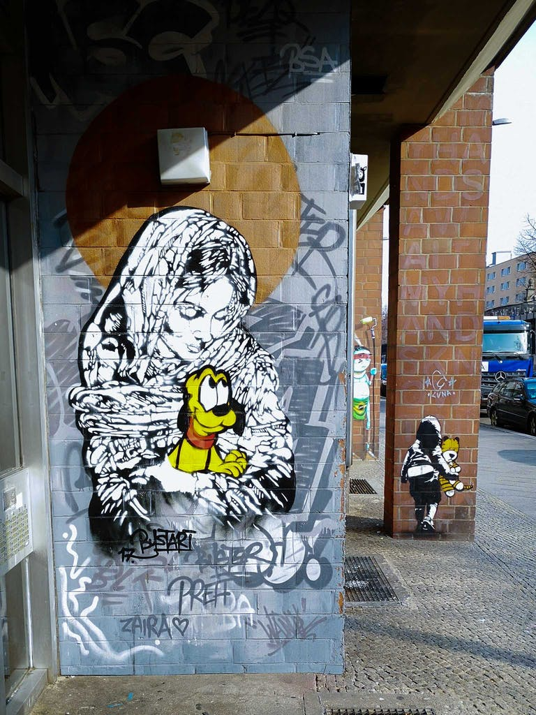 Another work by Bustart at the same location, showing the virgin Mary in black and white holding Pluto in her arms.