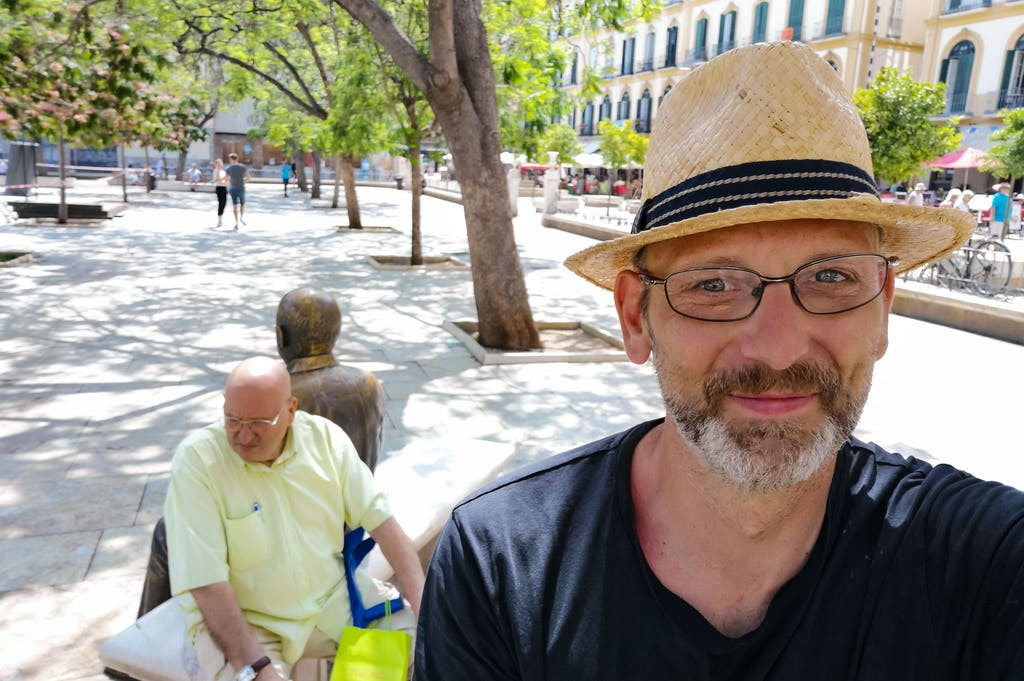Selfie with straw boater, Picasso statue with a local sitting beside him. in the backgound.