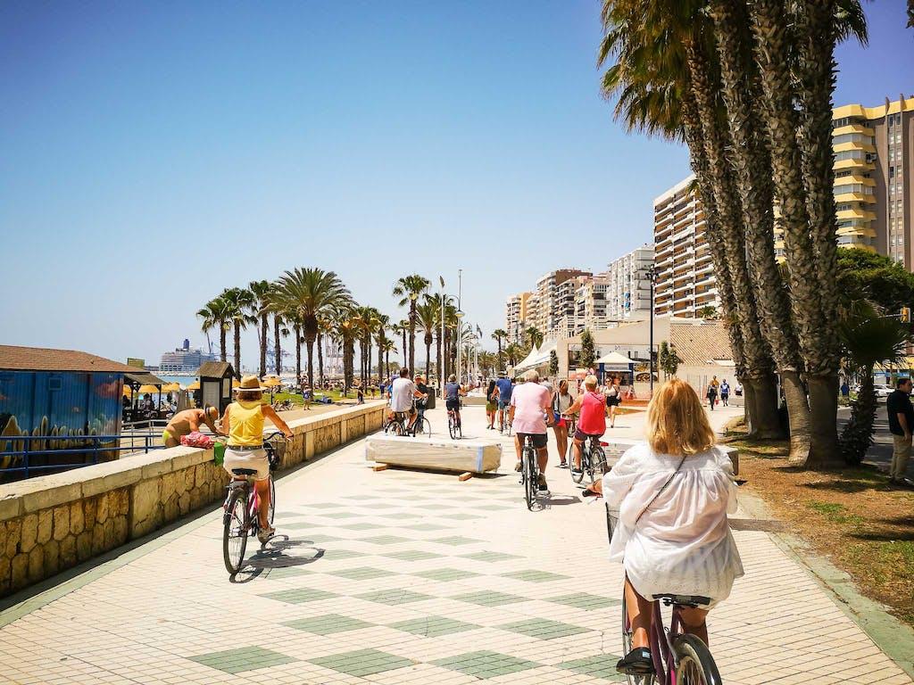 Cyclists riding on the Malaga beach promenade at the Playa la Malaqueta.