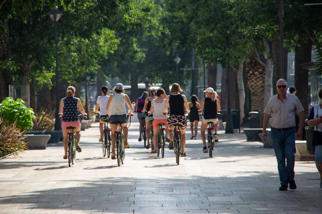Group of a dozen cyclists riding on the sidewalk of PAseo de Parque in Malaga.