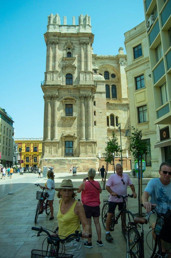 """Cyclists in front of Santa Iglesia Catedral Basílica de la Encarnación, Malaga cathedral, sometimes called """"La Manquita"""" ~ the one-armed lady."""