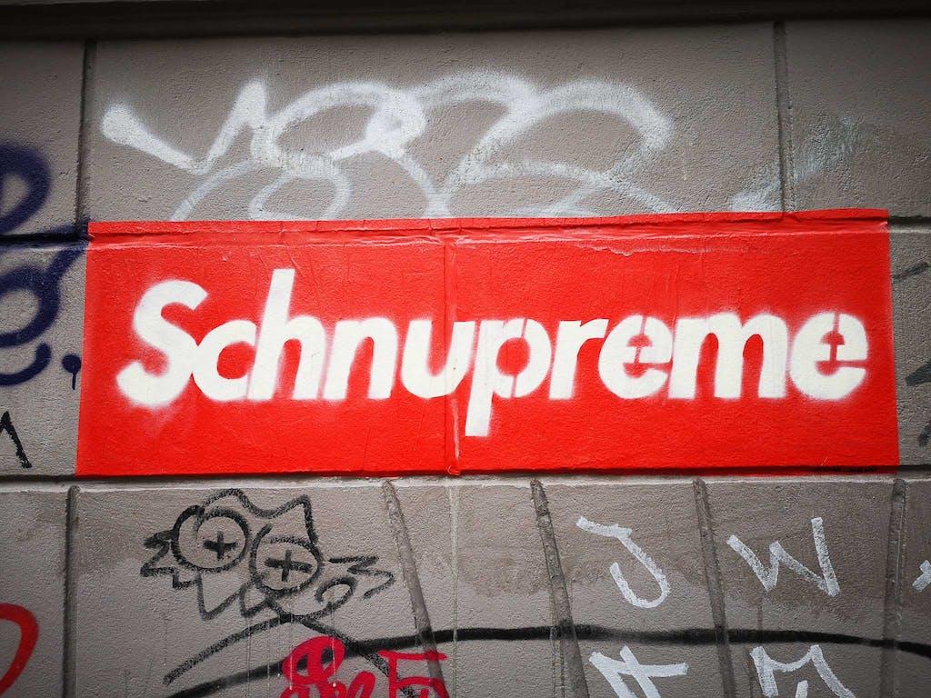 Schnupreme - white on red, paste-up - by Senor Schnu in Neukoelln's Richardstraße, Café Botanico.