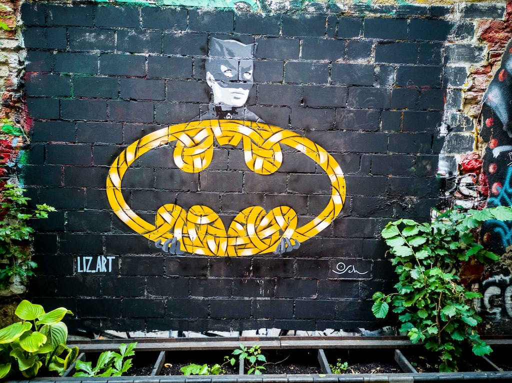 Mural in Haus Schwarzenberg with a bat signal by Otto Schade and a cat woman paste-up by liz.art