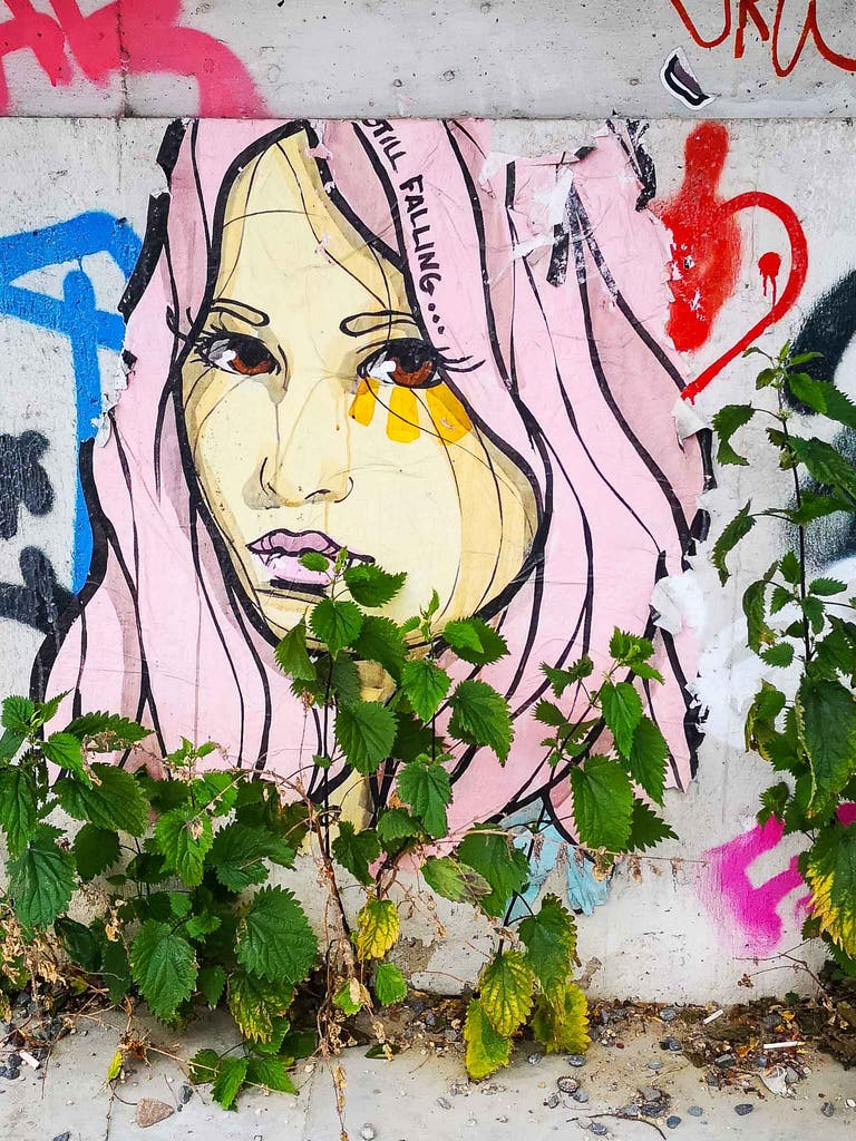 Paste-Up of a female face with the words Still falling written in her hair. Local artist El Bocho.