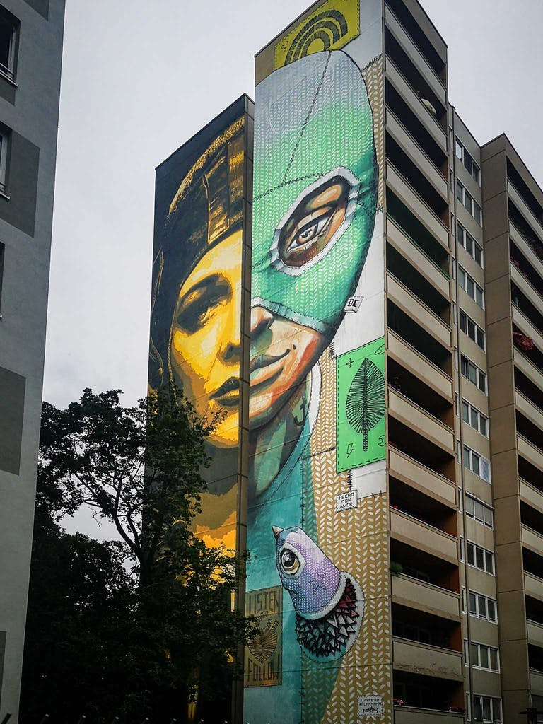 Diptych on a giant wall in Berlin Tegel; one side showing a female pilot, the other a female Luchadora (wrestler).